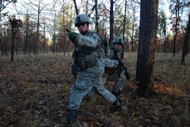 Muskogee, Okla. native Sgt. Adam Farmer (left) of C Company, 2nd Battalion, 325th Airborne Infantry Regiment, 2nd Brigade Combat Team, 82nd Airborne Division, calls for his squad to move out during movement to assault an objective as part of a live fire exercise at Fort Bragg Dec. 5.
