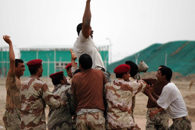 The Soldiers of Iraq's newest unit, the 41st IA Brigade, hoist up one of their American instructors after completing an obstacle course on their graduation day.