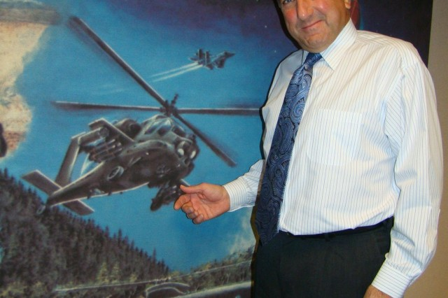 Paul Bogosian, program executive officer for aviation, stands in front of the iconic Army aviation mural that hangs in the PEO Aviation headquarters.