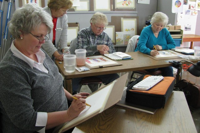 Fine arts instructor Margaret Chapman, standing in background, answers questions about a watercolor piece of three angels that student Lindy Kewatt is working on in the watercolor class now being taught at the June M. Hughes Arts & Crafts Center. Also working on their interpretations of the three angels are Trish Mullins, in the foreground, and Aleta Graham, at right.