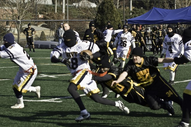 Navy wide-receiver Darrius Rhodes bypasses Army flag football rivals on the field Dec. 6 during the twelfth annual Army-Navy game at Yongsan Garrison, Seoul, Republic of Korea.