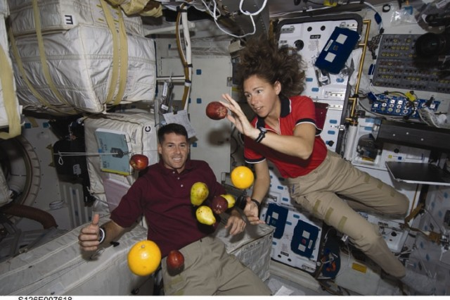 Astronauts Shane Kimbrough and Sandra Magnus, both STS-126 mission specialists, are pictured with fresh fruit floating freely on the middeck of Space Shuttle Endeavour during flight day three activities.