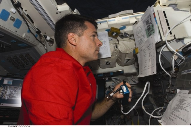 Astronaut Shane Kimbrough, STS-126 mission specialist, uses a communication system on the aft flight deck of Space Shuttle Endeavour while docked with the International Space Station.