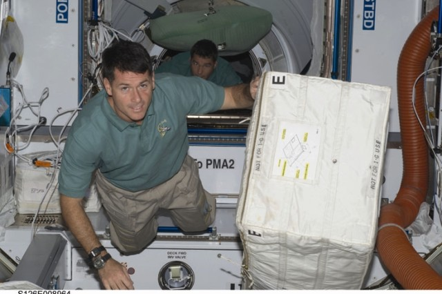 Astronaut Shane Kimbrough, STS-126 mission specialist, moves a stowage bag in the Harmony node of the International Space Station while Space Shuttle Endeavour remains docked with the station. Astronaut Steve Bowen, mission specialist, is visible in the background.