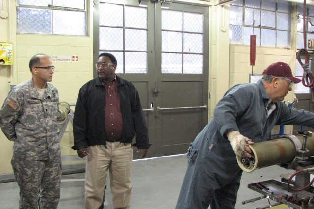 Lt. Col. Johnny Figueroa, Product Manager-Demil, listens as Clyde Hill, munitions operator, guided missile supervisor for Anniston Munitions Center's, missile recycling center, explains the recycling process for a Tube-launched, Optically-tracked, Wire-guided (TOW) missile on Dec. 4 in Anniston, Ala.