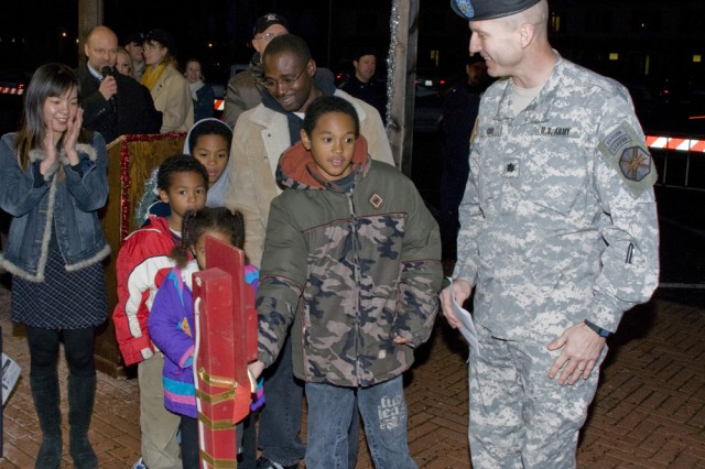 The McKinney family pulls the switch to illuminate the Camp Darby, Italy, Christmas tree during a lighting ceremony Dec. 5. Sgt. Tony McKinney, assigned to the 497th Transportation Company, returned home on rest and recuperation leave from Iraq to surprise his family at the annual community-wide event.