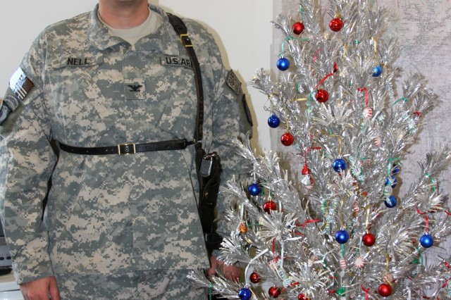 Col. Roger Nell, command judge advocate with Task Force Warrior, stands in his office at Bagram Airfield, Afghanistan, beside an artificial Christmas tree that has served alongside father or son on three wartime missions and six Christmas deployments.