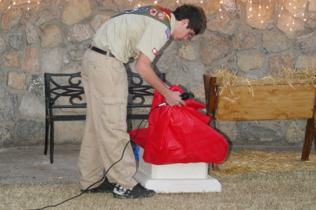 Paul Doran lifts a tarp to unveil a plaque honoring fallen servicemembers. Doran's Eagle Scout project, a memorial consisting of the plaque, a bench and a living Christmas tree, was unveiled on Dec. 7, at Fort Bliss' Center Chapel 2.
