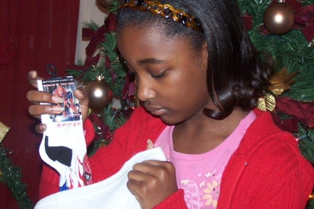 LaVencia V. Gaines, 10, daughter of Yolanda J. Edwards, a receptionist with the garrison Office of the Staff Judge Advocate, Fort McPherson, Ga.,  fills an extra large stocking on the evening of Dec. 8, 2008, from a table full of donated socks she collected this season for hospitalized children.