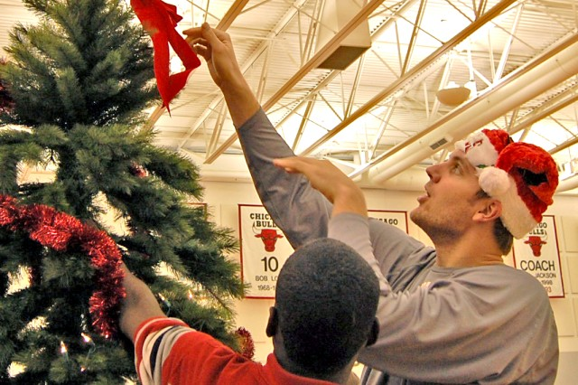 Chicago Bulls Forward, Andres Nocioni, puts the finishing touches on a Christmas tree.  Members of the Bulls assisted the children in decorating several Christmas trees during the party.