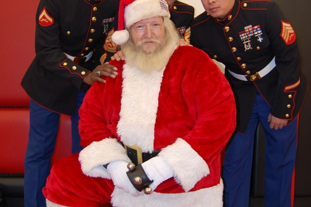 Santa Claus poses with Lance Cpl. James Dillingham, (left), Gunnery Sgt. Michael Michalski, (center) and Sgt. Matthew Shimizu, (right) at a holiday party for deployed military member's children sponsored by the Chicago Bulls.