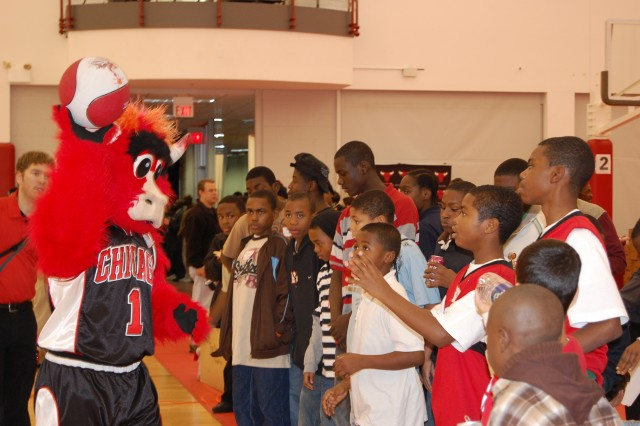 The Chicago Bulls mascot, Benny, throws the basketball to a crowd of fans who take turns tossing the ball into the basket on the other side of the gymnasium.