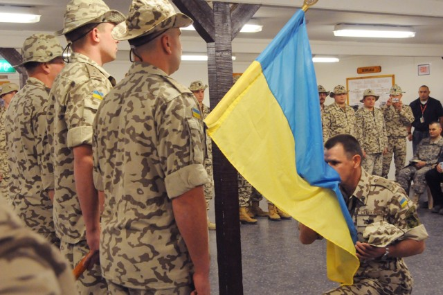 Col. Henadii Lachkov, commander of the Ukrainian contingent in Diwaniya, Iraq, kisses his countryAca,!a,,cs flag during an end of mission ceremony at Camp Echo, Dec. 9.