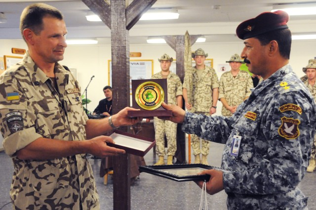 Col. Henadii Lachkov, commander of the Ukrainian contingent in Diwaniya, presents a certificate and gift to Lt. Col. Abbass, a member of the Qadisiya Province Iraqi Police, during an end of mission ceremony at Camp Echo, Dec. 9.