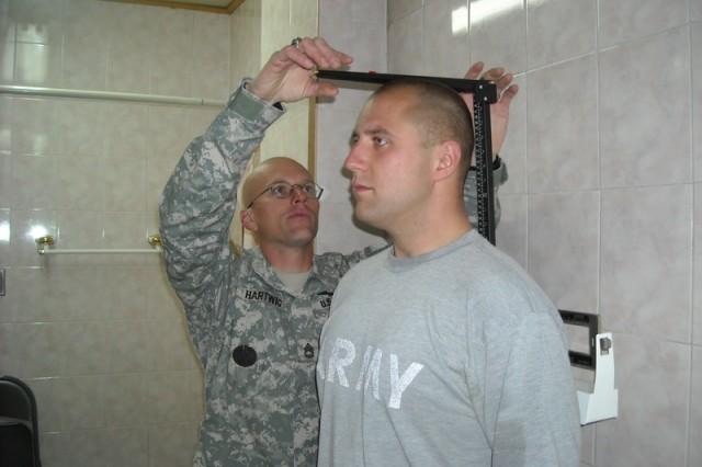 Sgt. 1st Class Benjamin Hartwig measures the height of Sgt. Jesse Jacka.