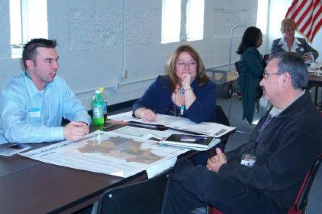 Ramon Rivero of the TACOM LCMC Command Rock Island, Ill., left, talks with Matt Tarasenko and Kim Murphy of Detroit Arsenal at an information session held at Rock Island Dec. 2 to learn more about Southeast Michigan.  The 2005 BRAC Commision recommendation relocates all of TACOM Rock Island's 1,200 jobs, most to Detroit Arsenal, by September 2011.