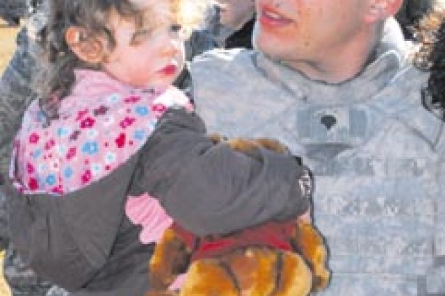 Specialist Michael Parker, Co. A, 4th Battalion, 64th Armor, greets his 2-year old daughter, Alexa, after returning from Iraq, Dec. 8 at Cottrell Field.