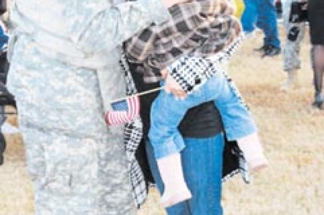 Home for the holidays - Specialist Jaruz Perez, assigned to the 6th Squadron, 8th  Cavalry Regiment, 4th Brigade Combat Team, hugs his wife, Monica, and daughter, Sindy, at a welcome home ceremony at Cottrell Field, Dec. 5, after returning from a 14-month deployment.