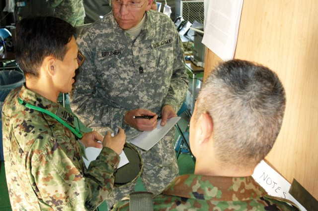 """Command Sgt. Maj. Fred Bruner of Richmond, Va., coordinates for a mission with his counterparts in the Japanese Ground Self Defense Force."""""""