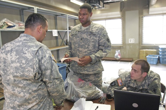 Staff Sgt. Robert McDuffie, a light-wheel mechanic, and Sgt. Joseph Enoch, a laundry and bath services specialist, both with Task Force 35, assist a fellow Soldier with picking up his laundry.
