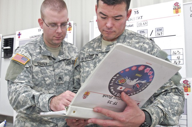 Staff Sgt. Jason Quigley (left), an intelligence analyst for Task Force 35, and Maj. Dan Reichard, the unit's supply operations officer, discuss security issues for the building that houses male Soldiers and the 35th's Tactical Operations