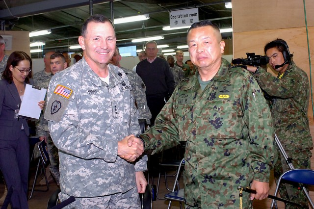 Lieutenant generals Benjamin R. Mixon, commander U.S. Army Pacific, and Kazushi Izumi, commander Japanese Ground Self Defense Force Eastern Army, greet each other, Tuesday, Dec. 9, 2008, at USARPC Operations Command Post before getting their morning brief on bilateral training exercise Yama Sakura 55. This year's exercise, which runs from Nov. 30 to Dec. 14, marks the 27th year Japanese and American forces have tested their ability to work together and their capability to defend the Japanese islands. This also is the first time USARPAC has taken on the role of being the operational command post. Yama Sakura is an annual bilateral, computer-based command post exercise conducted by the United States and Japan. This year, more than 1,000 Army, Air Force, Navy and Marine personnel are here interacting with their counterparts from the Japan ground, air and maritime self defense forces. Yama Sakura is intended to improve combat readiness of both forces, while continuing to improve security relations between the two nations. Camp Asaka, 12 miles west of Tokyo, is headquarters for the JGSDF's Eastern Army, and it's the main defense-force hub for Tokyo and 10 surrounding prefectures. (U.S. Army photo by Sgt. 1st Class Roy Henry)