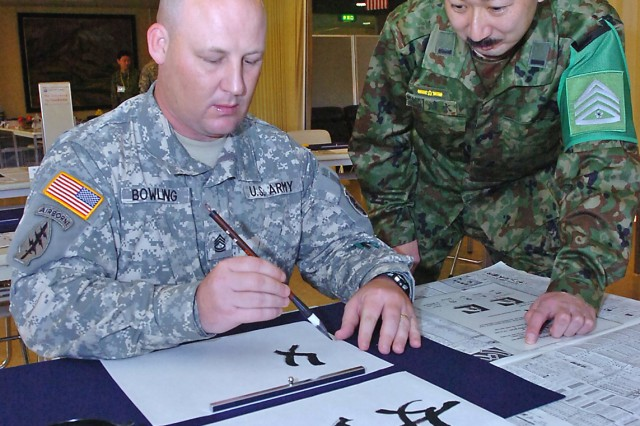 Army Sgt. 1st Class Tony Bowling (left), first sergeant for Headquarters Company, 8th Theater Sustainment Command out of Fort Shafter, Hawaii, gets a lesson in the art of Calligraphy from Sgt. Maj. Kazuhiko Shimizu of the JGSDF's 104th General Support Battalion, Dec. 3, 2008, at the camp's Freedom Room. Bowling, who hails from Canton, Ill., is one of more than 1,000 American Soldiers, Sailors, Marines and Airmen participating in Yama Sakura 55, along with their counterparts from the Japanese ground, air and maritime services. Yama Sakura is a bilateral U.S.-Japan, computerized command post exercise designed to better the defense of Japan, and to protect each country's interests throughout East Asia. Many actually started arriving setting up operations about three weeks prior to the exercise starting. This year's exercise marks the 27th year Japanese and American forces have tested their ability to work together and their capability to defend the Japanese islands. YS55, which officially began, Dec. 7 with a ceremony on the grounds of the JGSDF Transportation School, runs until Dec. 14. (U.S. Army photo by Sgt. 1st Class Roy Henry)