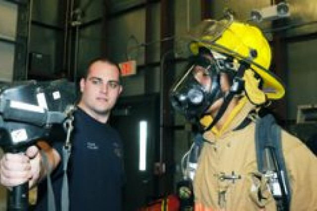 Chad Vukas, a firefighter with Fort Riley Emergency Services, shows Brittany Greene how a thermal imager is used to locate people and other heat sources in a smoke-filled room. Greene was allowed to shadow firefighters Dec. 5 at Fire Station No. 4.