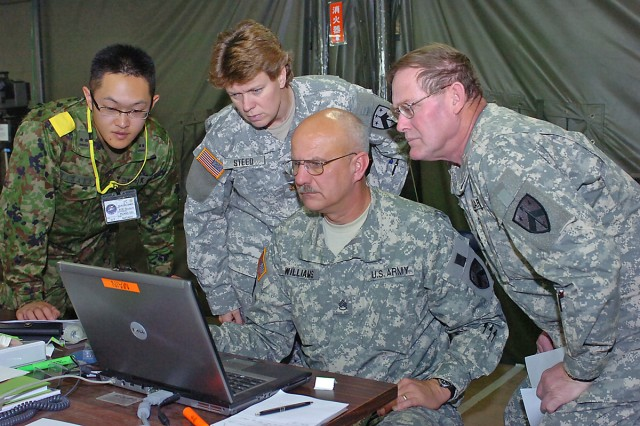 """From the left 1st Lt. Satoshi Masaka, Japanese Ground Self Defense Force (JGSDF) Plans Division-Northeast Army and members of the Tennessee National Guard's 230th Theater Sustainment Brigade, engineer Maj. Jennifer Steed; military intelligence systems analyst Staff Sgt. Charles Williams; and maintenance NCOIC Master Sgt. David Spence track and verify the movement of Japanese forces, Monday, Dec. 8, 2008, at the U.S. Army Pacific Operations Command Post during bilateral training exercise Yama Sakura 55. This year's exercise, which runs from Nov. 30 to Dec. 14, marks the 27th year Japan and American forces have tested their ability to work together and their capability to defend the Japanese islands. This also is the first time USARPAC has taken on the role of being the operational command post. Yama Sakura is an annual, computer-based command post exercise conducted by the United States and Japan. This year, more than 1,000 Army, Air Force, Navy and Marine personnel are here interacting with their counterparts from the Japan ground, air and maritime self defense forces. Yama Sakura is intended to improve combat readiness of both forces, while continuing to improve security relations between the two nations. """"The interest of our countries in defending Japan and keeping the peace in the region requires us to become more familiar with how we will conduct bilateral operations if a situation happens,"""" Masaka said. """"It's a great privilege to be working along side my American counterparts in this endeavor."""" Steed, Williams and Spence echoed his sentiments. """"Being here and taking part in YS 55 also is a great honor for us,"""" Steed said. """"Through this exercise, we [the U.S. and Japanese military] create a better understanding of how we'll work together on the battlefield to halt any threat to the people of this great island nation."""" Camp Asaka, 12 miles west of Tokyo, is headquarters for the JGSDF's Eastern Army, and it's the main defense-force hub for Tokyo and 10 surrounding"""