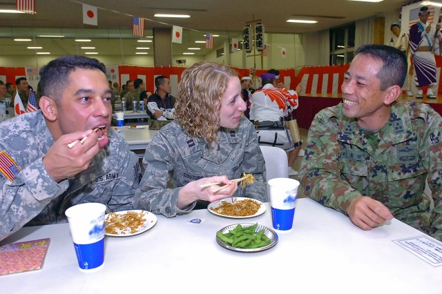 From the left Major Max Moore, chief of future plans for Chuqiak-based U.S. Army Alaska, and Air Force Capt. Melissa Couture enjoy the local cuisine at the camp's Friendship Hall, Dec. 4, 2008, with Capt. Norihisa Yonada, training officer for the Japan Ground Self Defense Force 1st Airborne Brigade. Moore, who hails from Queens, N.Y., is among the more than 1,000 American Army, Navy, Marine and Air Force personnel participating in Yama Sakura 55, along with their counterparts from the Japan ground, air and maritime services. Yama Sakura is a bilateral U.S.-Japan, computerized command post exercise designed to better the defense of Japan, and to protect each country's interests throughout East Asia. Many actually started arriving setting up operations about three weeks prior to the exercise starting. This year's exercise marks the 27th year Japan and American forces have tested their ability to work together and their capability to defend the Japanese islands. YS55, which officially began Dec. 7, with a ceremony on the grounds of the JGSDF Transportation School, runs until Dec. 14. (U.S. Army photo by Sgt. 1st Class Roy Henry)