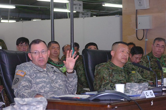 Lieutenant Gen. Benjamin R. Mixon, commander U.S. Army Pacific, makes a point during the morning brief he and Lt. Gen. Kazushi Izumi, commander Japan Ground Self Defense Force Eastern Army receive each day at USARPAC Operations Command Post on bilateral training exercise Yama Sakura 55. This year's exercise, which runs from Nov. 30 to Dec. 14, marks the 27th year Japan and American forces have tested their ability to work together and their capability to defend the Japanese islands. This also is the first time USARPAC has taken on the role of being the operational command post. Yama Sakura is an annual bilateral, computer-based command post exercise conducted by the United States and Japan. This year, more than 1,000 Army, Air Force, Navy and Marine personnel are here interacting with their counterparts from the Japan ground, air and maritime self defense forces. Yama Sakura is intended to improve combat readiness of both forces, while continuing to improve security relations between the two nations. Camp Asaka, 12 miles west of Tokyo, is headquarters for the JGSDF's Eastern Army, and it's the main defense-force hub for Tokyo and 10 surrounding prefectures. (U.S. Army photo by Sgt. 1st Class Roy Henry)