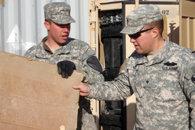Appleton, Wis. Native Pfc. Daniel Wolf (left), a radio transmission operator receives direction from veteran and Coshocton, Ohio native Spc. Robert Rizer (right), a Bradley driver, both from Headquarters and Headquarters Troop, 1st Brigade Combat Team, 1st Cavalry Division on the correct way to secure and brace the containers that transport the units equipment Dec. 5.  The Ironhorse Brigade is gearing up and shipping off their equipment in order to deploy early 2009.