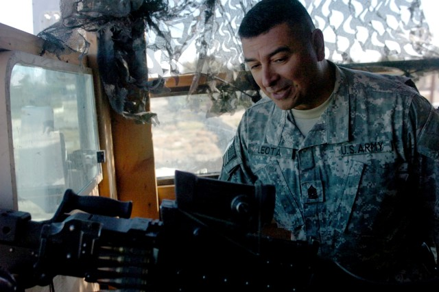 "Multi-National Division-North Command Sgt. Maj. Frank M. Leota, inspects a machine gun mounted atop the roof of the building of B. Company, 1st Battalion, 5th Infantry Regiment in Forward Operating Base, Gabe, Iraq Dec. 12. B. Company 1-5 Inf. Reg. is a part of the ""Arctic Wolves"" 1st Brigade, 25th Infantry Division Stryker Brigade Combat Team."