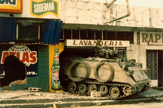 A U. S. armored M-113 personnel carrier finds shelter in  a Panama City laundramat.The use of heavy forces mounted in M-113's were key to success in combat in the city, providing firepower, protection, and mobility (Maxwell Thurman Photograph Collection).