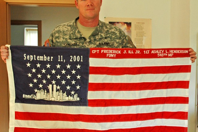 Sgt. JonPaul Conover, family readiness liaison with the 501st Military Police Company at U.S. Army Garrison Wiesbaden, Germany, displays a flag made in commemoration of Sept. 11, 2001, with the names of his uncle, a firefighter killed that day, and his first lieutenant, killed while Conover served with her in Iraq.