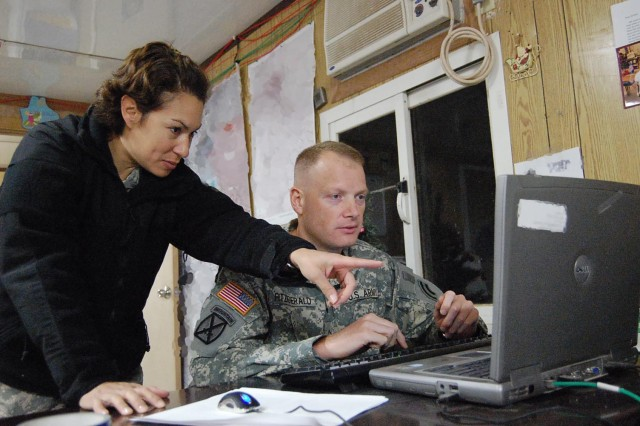 Pfc. Steven P. Fitzgerald and his fiancée, Spc. Viviana B. Molina, of the 3-142nd Assault Helicopter Battalion, review intelligence reports before a briefing in Iraq. Fitzgerald, an 18-year veteran of the New York City Fire Department, joined the National Guard when he was 41 years old.