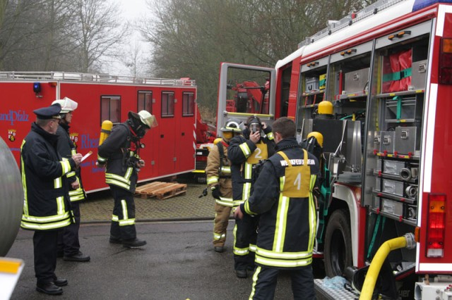 Officials from the state of Rheinland-Pfalz fire and civil protection academy (Landes Feuerwehr-und Katastrophenshutzschule) in Koblenz evaluate a joint team of U.S. Army and German firefighter gear up for skills testing held as part of the final exams Dec. 10-11 at the academy