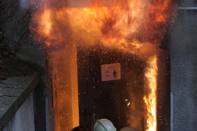 With helmets barely visible, a U.S. Army and German firefighter open a door to a structural fire during skills testing as part of the training course Dec. 10-11 at the Officials from the Rheinland-Pfalz fire and civil protection academy in Koblenz.