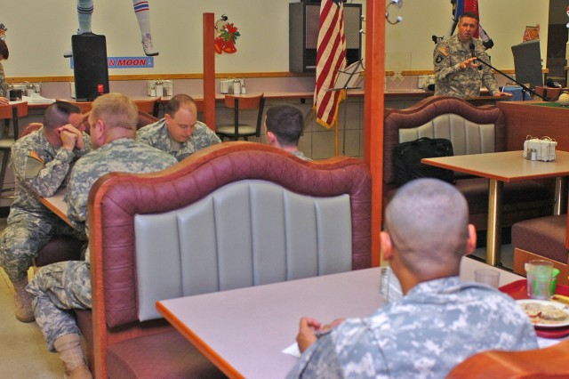 Chicago native Maj. Ken Carlson, chaplain, 15th Sustainment Brigade, 13th Sustainment Command (Expeditionary), talks to Soldiers Dec. 9 at the Freeman Café Dining Facility during a prayer breakfast hosted by the brigade. Carlson told the Soldiers there was a time for everything, and now was their opportunity to be strengthened together spiritually as an Army family.