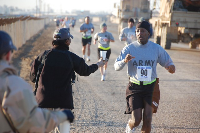 A Soldier reaches out for water during the Satellite Honolulu Marathon at Camp Taji, northwest of Baghdad, Dec. 14. The satellite marathon was run on Camp Taji twelve hours before the Honolulu Marathon.  (U.S. Army photo by Maj. Al Hing, 2nd SBCT PAO)
