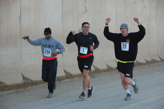 Soldiers let out a cheer during the grueling 26.2 mile course around Camp Taji, northwest of Baghdad, during the Satellite Honolulu Marathon, at Camp Taji, northwest of Baghdad, Dec. 14.  (U.S. Army photo by Maj. Al Hing, 2nd SBCT PAO)