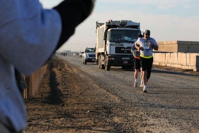 """– Runners near a water point during the Satellite Honolulu Marathon at Camp Taji, northwest of Baghdad, Dec. 14. Approximately 160 runners participated in the race, sponsored by the 2nd Stryker Brigade Combat Team, """"Warrior,"""" 25th Infantry Division, Multi-National Division – Baghdad. The brigade is based out of Schofield Barracks, Hawaii. (U.S. Army photo by Sgt. Jacob Smith, combat camera)"""