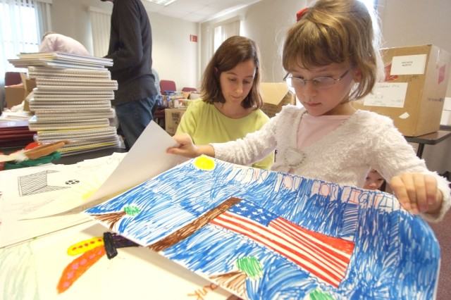 Jennifer Schramm and her daughter Kelly look over drawings for deployed Soldiers to select one to put in a box they put together for husband and father Maj. Matthew Schramm who is currently deployed to Iraq. Items for deployed Soldiers were collected by the Hearts Apart group, an organization for families of deployed Soldiers and civilians under the Army Community Service umbrella.