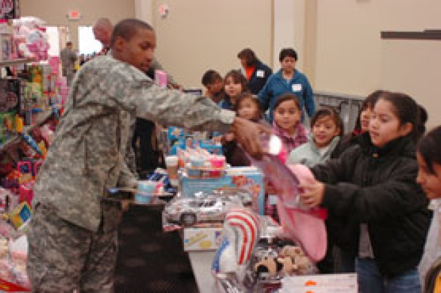 Spc. Troy Norman, a water purification specialist with Headquarters and Headquarters Battery, 3rd Battalion, 43rd Air Defense Artillery, hands a toy to Estephany Florentino, 8, a third-grader at Desert Wind Elementary, during a toy-drive giveaway Friday at the Abundant Living Faith Center. More than 11,000 toys were collected and distributed to underprivileged students from 14 local schools.