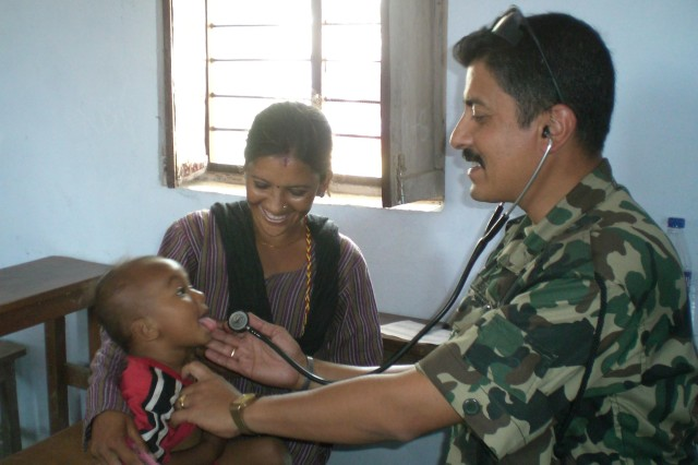 Col. (Dr.) Arun Neopane, a pediatrician from Nepal Army, performs assessment on a local child.