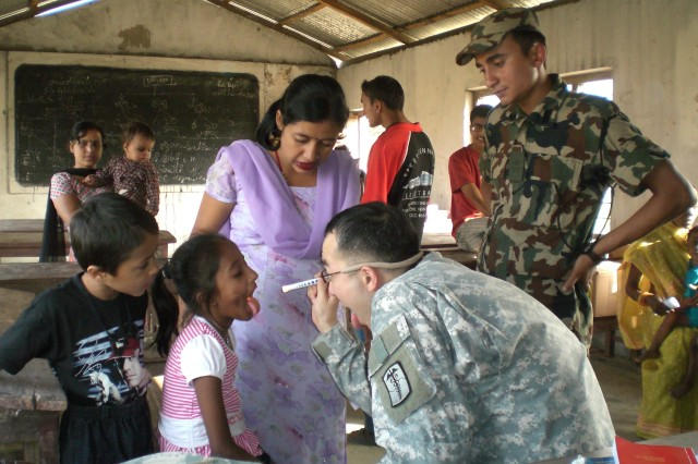 A USARPAC dentist examines a young Nepalese girl's teeth during the joint US-Nepal medical readiness training exercise.  The goal of the exercise is to increase the interoperability between the two nations while expanding the knowledge base of the medical professionals taking part in the mission.