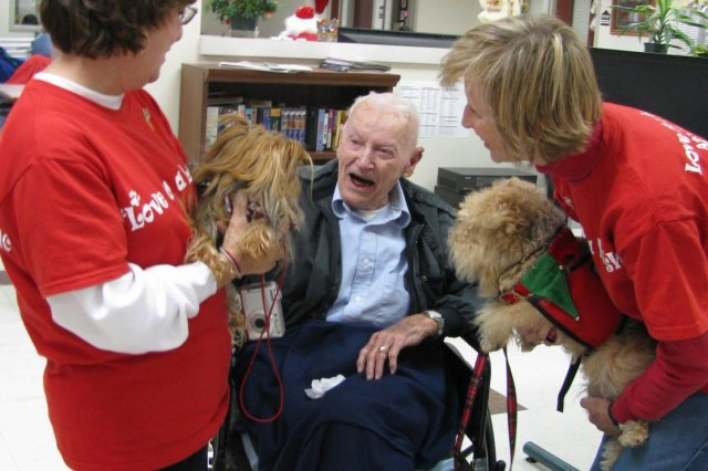 """World War II veteran Douglas """"Monroe"""" Mullican breaks out in a big smile as he talks to his canine visitors, Miss Sophie with her owner Sheila Banks to the left and Sailor with his owner Sharyl Groscost. The two therapy dogs visit nursing homes and schools as members of Love on a Leash Therapy K9s. They were among several dogs and their owners who visited veterans at the Tut Fann Veterans Home on Dec. 9."""