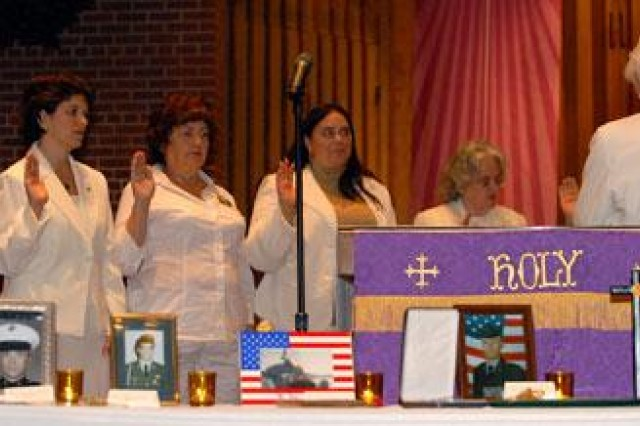 Northeast Kansas Gold Star Mothers Chapter officers take their oath and receive instruction from Betty Pulliam, right, Vietnam War Gold Star Mother, during the NE Kansas GSM chartering ceremony Dec. 14 at Fort Leavenworth's Main Post Chapel.