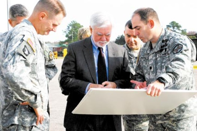 Colonel Don Galli, commander of the Combat Aviation Brigade (left) and Lt. Col. Daniel Whitney, the garrison commander of Hunter Army Airfield (right) talk with the Honorable Nelson M. Ford, Under Secretary of the U.S. Army, Dec. 16 at Hunter Army Airfield.