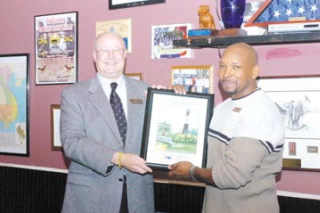 "Ed Wexler, CFC director for coastal Georgia, presents a framed picture of Tybee Island Lighthouse to Gene ""Roy"" Royster, administrative services assistant and installation representative for CFC.  Royster was congratulated for his service and achievements during a luncheon at Hinesville's Western Sizzlin Steak House, Dec. 11 as he prepares to leave Fort Stewart for a new position at Fort Benning."